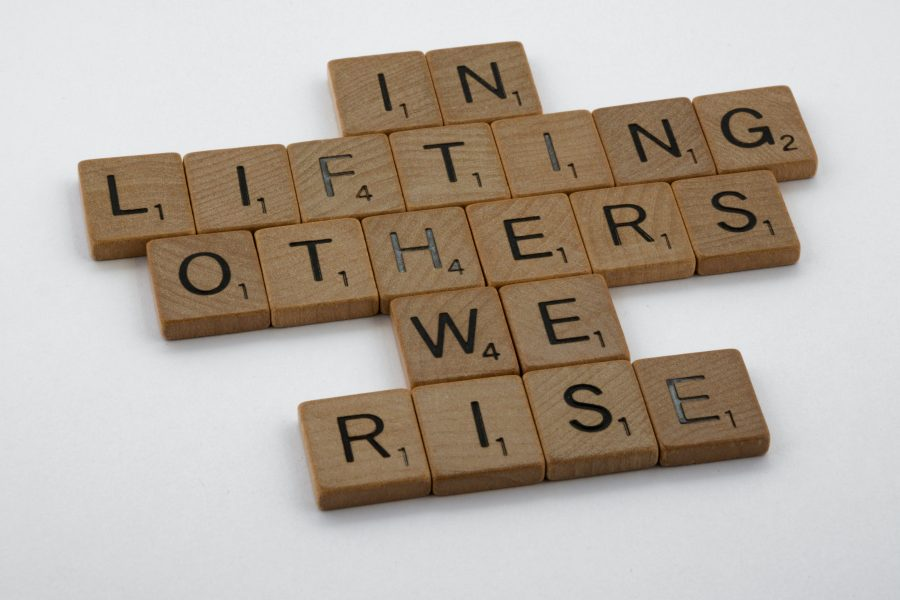 """Scrabble tiles spell out """"In lifting others, we rise."""""""