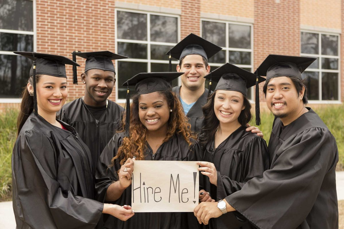 alt=a group of young graduates hold a sign saying hire me